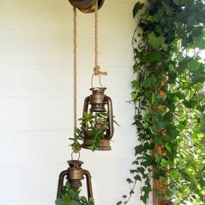 These charming old school lantern planters look amazing hanging from an antique pulley. Make your own with this super tutorial. #DIYHomeDecor #Planters #farmhousestyle